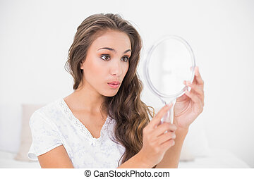 Surprised attractive brunette looking at mirror