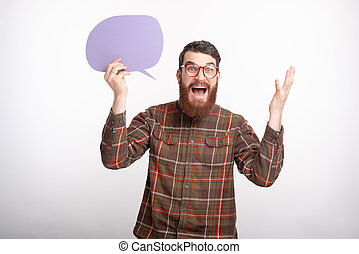 Surprised bearded man is holding a violet bubble speech over white background.