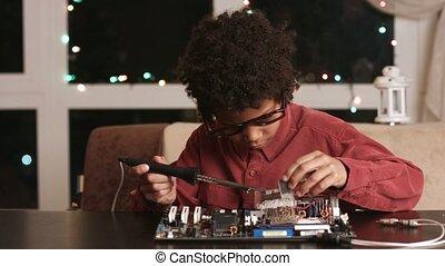 Surprised black boy fixing motherboard.