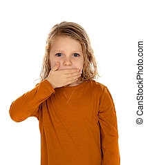 Surprised blond child with blue eyes covering his mouth