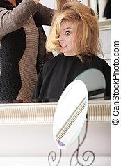 Surprised blond girl in hair salon