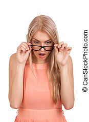 Surprised blond woman looking down over glasses - Portrait...