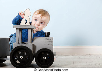 Surprised boy blond in a blue sweater sits on a wooden floor. One year old baby playing with wooden toys. He want to take cat. Toys are made of wood