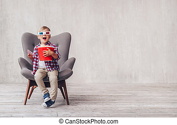Surprised boy in 3d glasses with popcorn