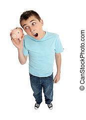 A pre teen boy shakes a money box piggy bank