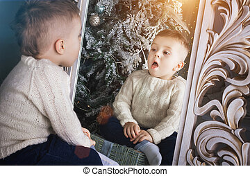 surprised boy sitting in front of the mirror