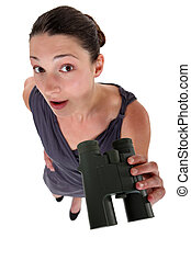 Surprised brunette holding binoculars