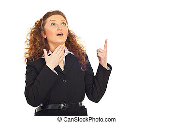 Surprised business woman pointing up