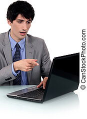 Surprised businessman pointing at his laptop