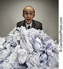 Surprised businessman reaches out from crumpled papers