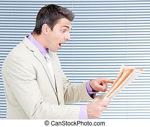 Surprised businessman reading a newspaper