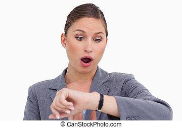 Surprised businesswoman checking her watch