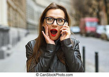 Surprised businesswoman talking on smart phone