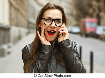 Surprised businesswoman walking down the street while talking on smartphone