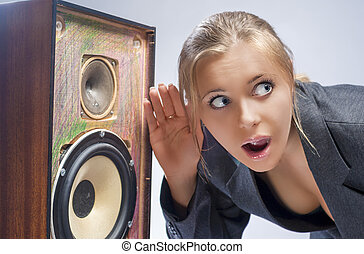 Surprised Caucasian Blond Female Harkens to Outdated Loudspeaker in Studio. Horizontal Image