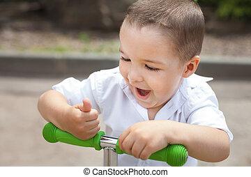 surprised child boy on a trike