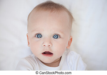 surprised child lies on his back on a white sheet