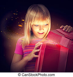 Surprised child with gift box. Happy little girl opening a...
