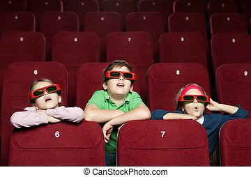 Surprised children watching a movie at the 3D cinema