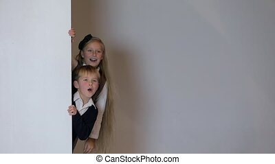 children looking out from behind white blank placard. -...