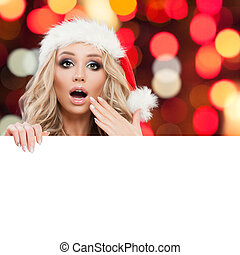 Surprised Christmas woman with white empty paper board on abstract bokeh background