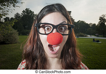 surprised clown girl with red nose at the park