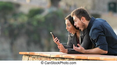 Surprised couple checking phone content in a balcony -...