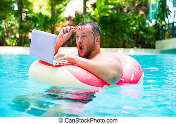 surprised Fat funny man in pink inflatable circle in pink glasses works on a laptop in a swimming pool.