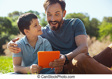 Surprised father watching a video with his son