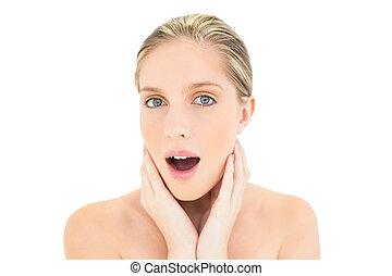 Surprised fresh blonde woman looking at camera