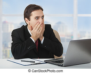 surprised frightened businessman looking at a laptop, his hands covering his mouth with fear and wonder, sitting at his desk