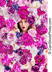 Surprised girl behind a flower wall