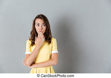 Surprised girl in dress standing with her hand covering mouth