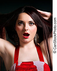 Surprised young woman straight long dark hair make up dark background