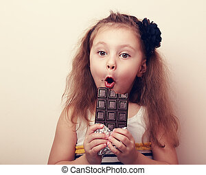 Surprised girl with open mouth holding chocolate and...