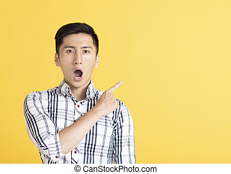 surprised handsome young man pointing