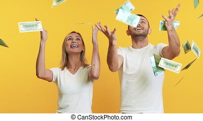 Surprised happy couple enjoying money rain falling down. Slow motion