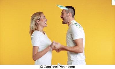 Surprised happy couple enjoying money rain falling down. ...