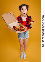 Surprised happy pretty young woman standing and holding pizza