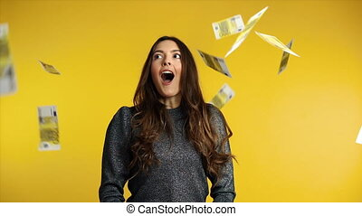 Surprised happy woman standing under money rain banknotes falling down