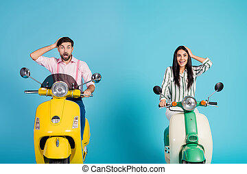 Surprised impressed tow people bikers man woman drive motor bike touch heads hands look incredible nature view scream wow omg wear formalwear clothes isolated over blue color background