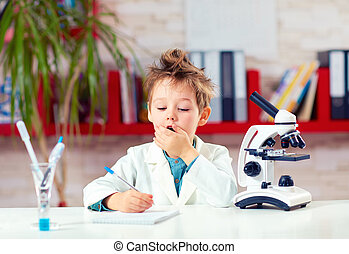 surprised kid, boy writing notes after experiment in school lab