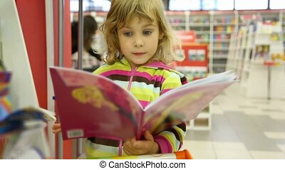 surprised little cute girl looking at child's book in bookshop