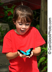 Surprised little girl holds a Ulysses Swallowtail