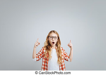 Surprised little girl standing isolated on grey background