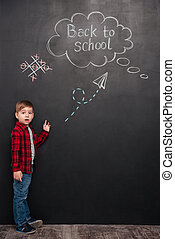 Surprised little schoolboy standing over chalkboard with drawings