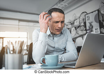 Surprised male watching at notebook computer