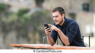 Surprised man finding content on a smart phone - Surprised...