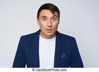 Surprised man looking at camera. Isolated on grey studio background