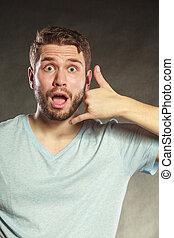 Surprised man showing call me gesture.